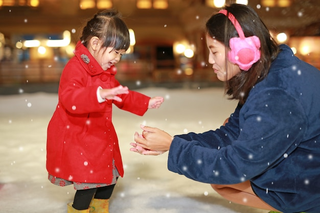 Happy family mother and adorable little girl has a fun in snow, winter time. Premium Photo