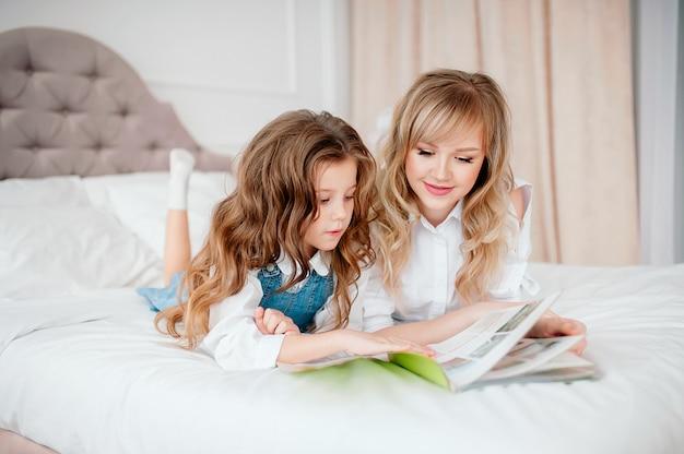 Счастливая семья, мать и дочь, чтение, держа книгу, лежа в кровати, улыбается мама няня, рассказывая смешные сказки, милый дошкольник ребенок девочка Premium Фотографии