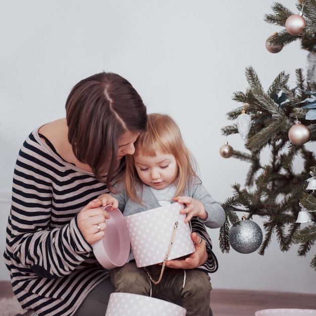 Happy family mother and baby decorate christmas tree Premium Photo