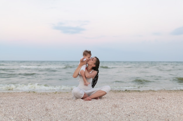 Happy family mother and child daughter doing yoga, meditate in lotus position on beach at sunset Premium Photo