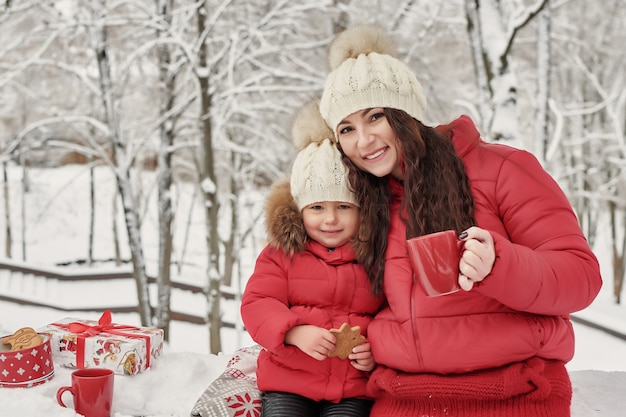 Happy family mother and child daughter on winter walk outdoors drinking tea. happy family mother and baby little child playing in winter christmas holidays. christmas family in winter park. Premium Photo