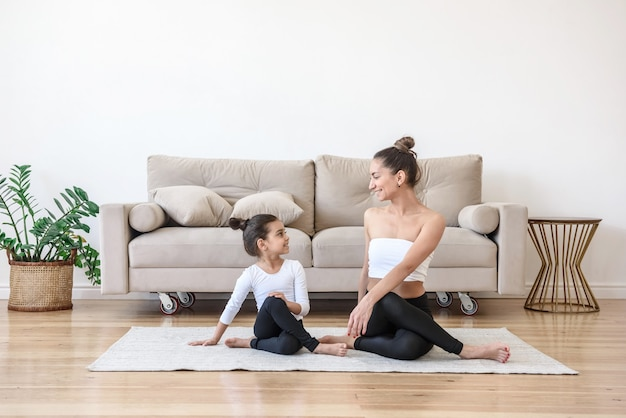Premium Photo | Happy family mother and daughter doing yoga at home