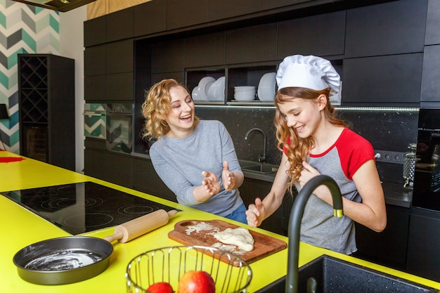 Happy family mother and daughter preparing dough, bake homemade apple pie in kitchen Premium Photo