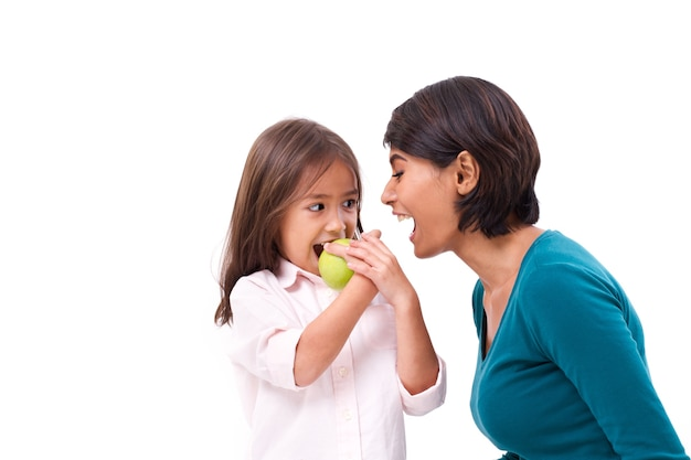 Happy family, mother and daughter with raw organic green apple, concept of healthy food Premium Photo
