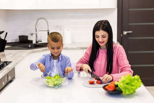Happy family mother with child son preparing vegetable salad at home Free Photo