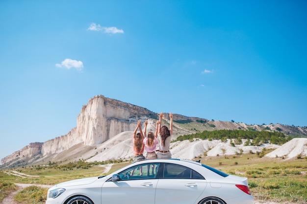 Счастливая семья мамы и детей на отдыхе в красивой природе во время автомобильного путешествия Premium Фотографии