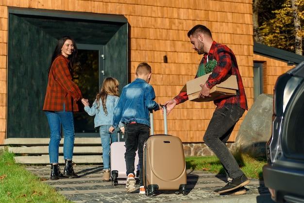 Счастливая семья родителей и двух детей несут чемоданы из машины в новый дом. концепция переезда. Premium Фотографии