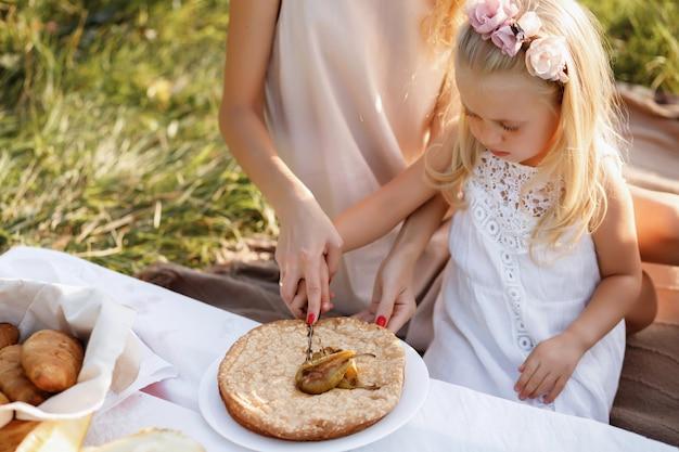 Счастливая семья на летнем пикнике режет пирог. крупный план Premium Фотографии