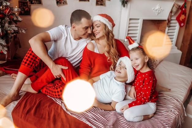 새해와 메리 크리스마스를 기다리는 침대에 행복한 가족 프리미엄 사진