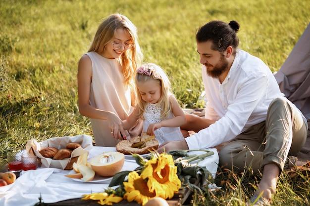 Счастливая семья на летнем пикнике режет торт Premium Фотографии