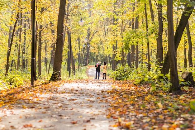 Счастливая семья на открытом воздухе осенью ребенок и мать и отец Premium Фотографии