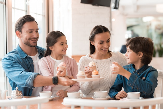 Happy family parents and kids share cakes in cafe. Premium Photo