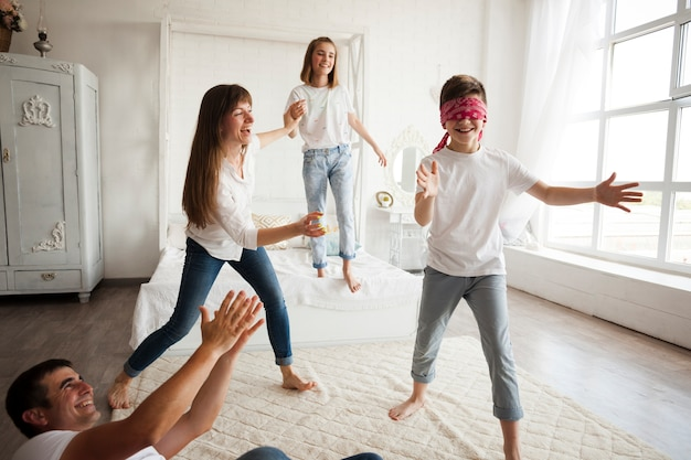 Happy family playing blind man's buff at home Free Photo