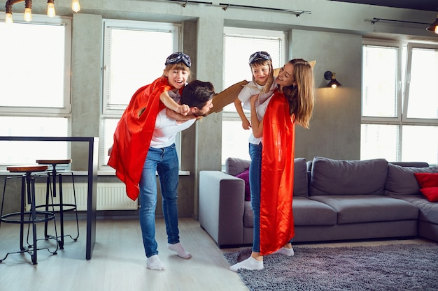 A happy family plays in superheroes indoors. Premium Photo