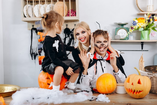 Happy family preparations to halloween. boy showing tongue and woman smiling Premium Photo