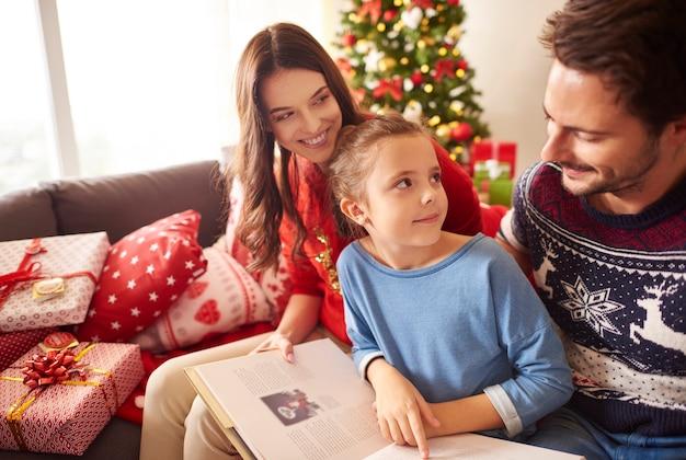 クリスマスに本を読んで幸せな家族 無料写真