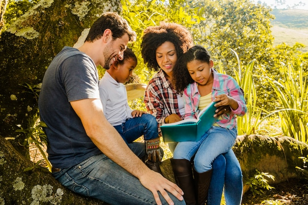 Happy family reading together under a tree Free Photo