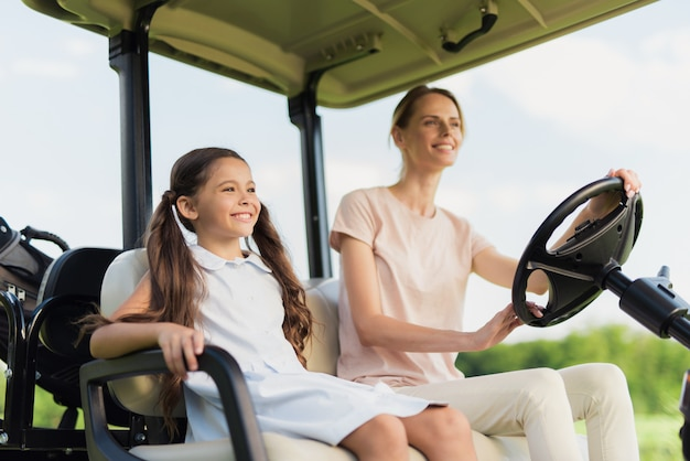 Happy family riding by golf car mum and daughter. Premium Photo