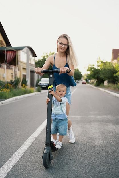 道路上の近所の幸せな家族乗馬スクーター。 無料写真