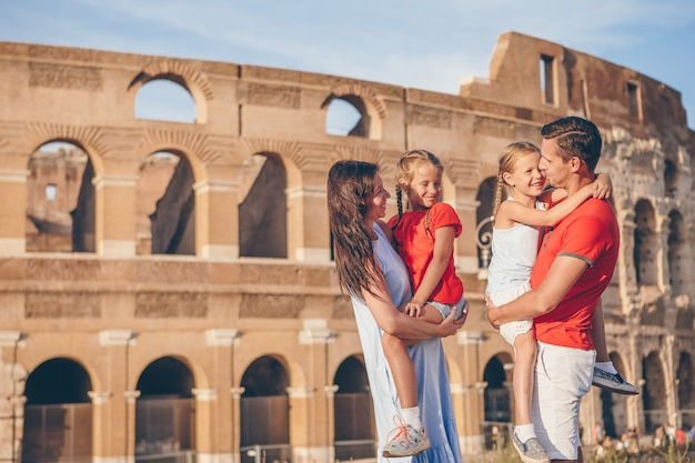 Happy family in rome over coliseum background. Premium Photo