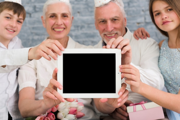 Happy family showing blank screen digital tablet Free Photo