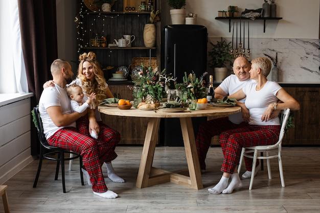 Счастливая семья, сидя за праздничным столом в канун рождества Premium Фотографии