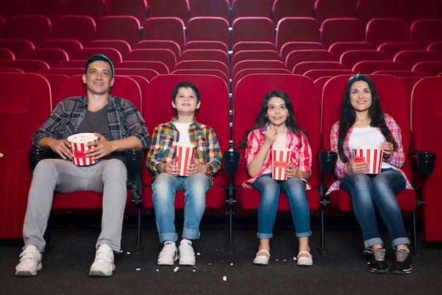 Happy family sitting in cinema Free Photo