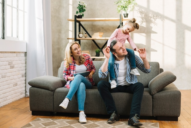 Happy family sitting on sofa in living room Photo | Free ...