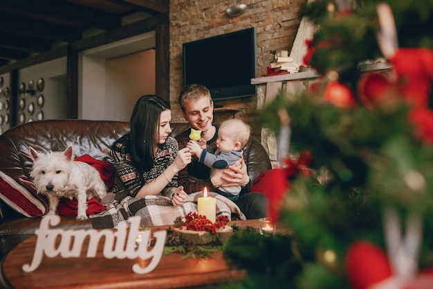 Happy family sitting on sofa with a defocused christmas tree in front and the word