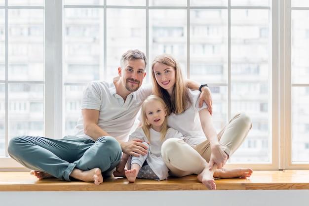Happy family sitting on windowsill together Premium Photo