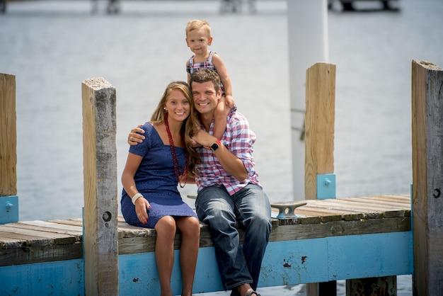 Famiglia felice che si siede su un sentiero in legno con il bambino sulla schiena dei padri Foto Gratuite