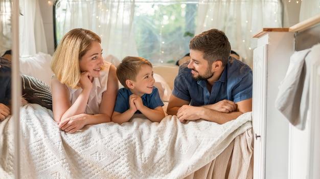 Счастливая семья, проводящая время в постели в караване Бесплатные Фотографии