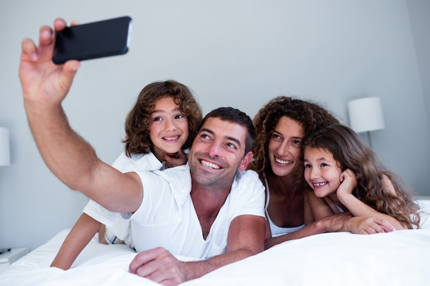 Happy family taking a selfie on bed Premium Photo