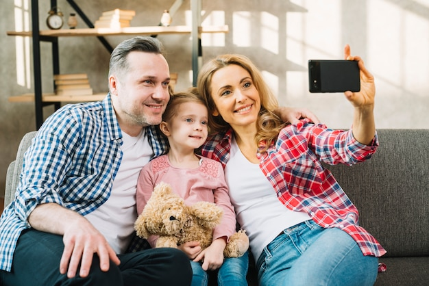 Happy family taking selfie on sofa Free Photo