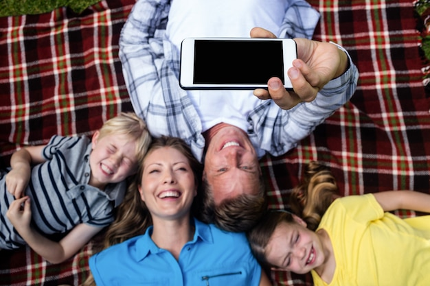 Happy family taking a selfie while lying in the park Premium Photo