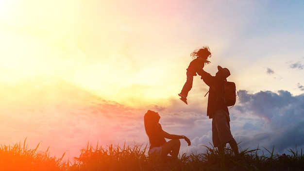 The happy family of three people, mother, father and child in front of a sunset sky. Premium Photo