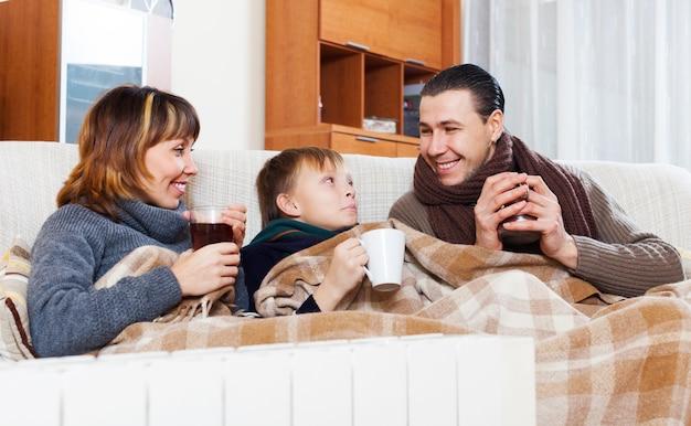 Happy family of three   warming near warm radiator Free Photo