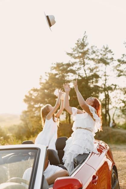 山の中を車で幸せな家族旅行。赤いカブリオレで楽しんでいる人。夏休みのコンセプト 無料写真