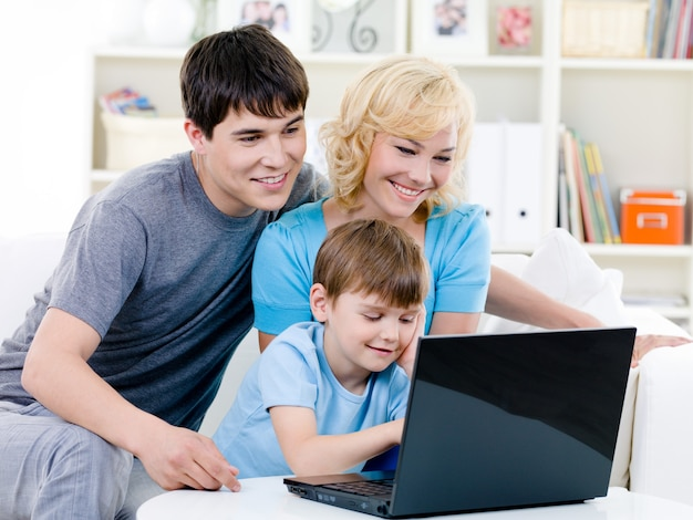Famiglia felice che per mezzo del computer portatile a casa Foto Gratuite