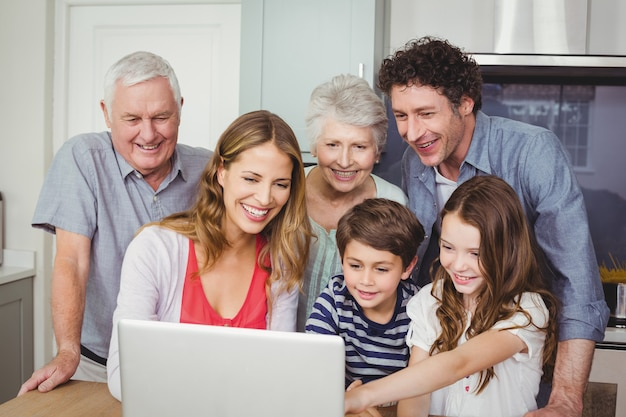 Happy family using laptop in kitchen Premium Photo