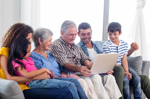 Happy family using laptop on sofa Premium Photo