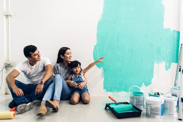 Happy family using a paint roller and painting walls in their new home Premium Photo