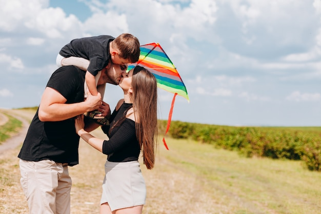Happy family walking outdoor. mother and father are kissing Premium Photo