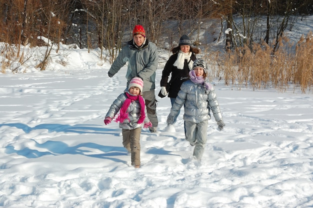 Happy family walks in winter, having fun and playing with snow outdoors on holiday weekend Premium Photo