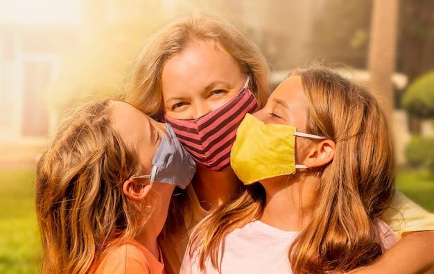 フェイスマスクを着て幸せな家族。マスクされた女の子は幸せなお母さんにキスします。 Premium写真