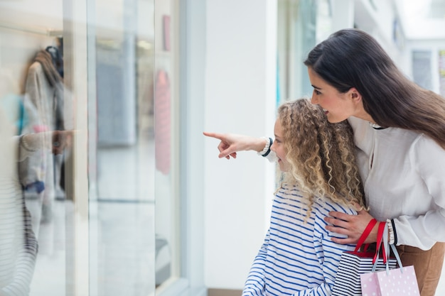 Happy family window shopping in mall Premium Photo
