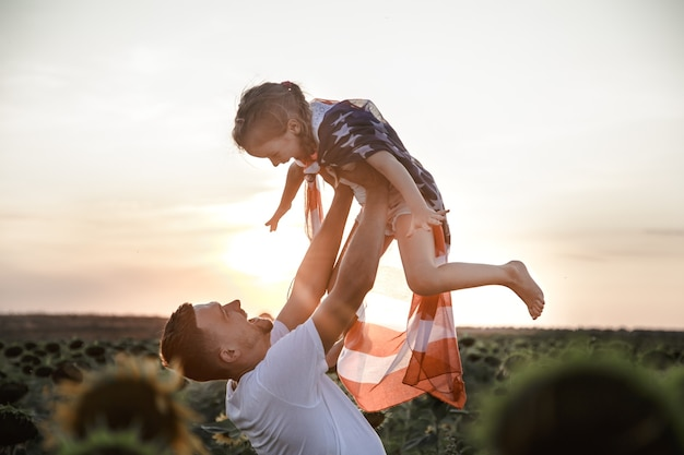 Una famiglia felice con una bandiera americana al tramonto. Foto Gratuite