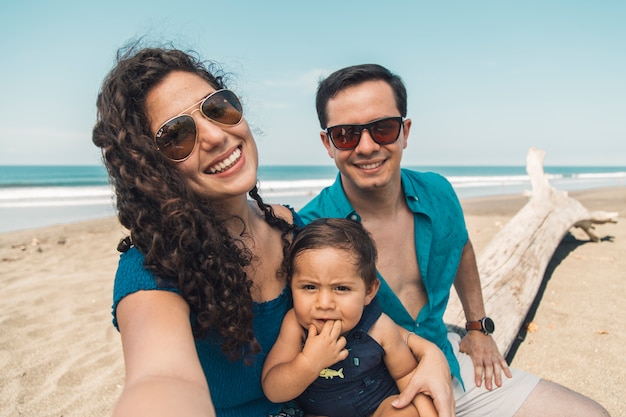 Happy family with baby taking selfie on beach in summer day Free Photo