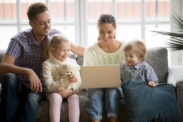 Happy family with children having fun using laptop on sofa Free Photo