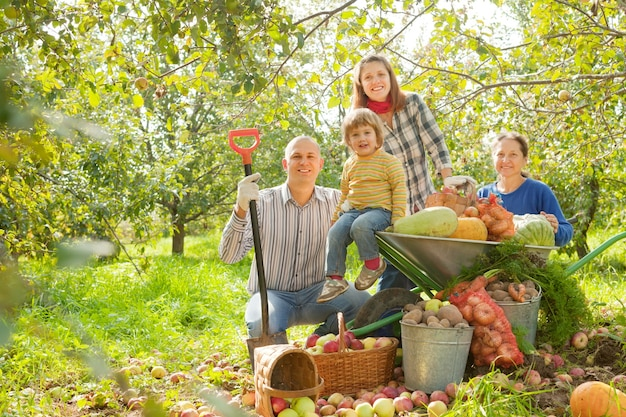 Happy  family with  harvest in garden Free Photo